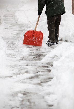Man shoveling snow from the sidewalk in front of his house after